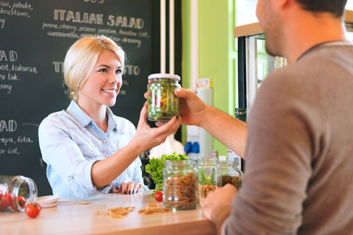 Customer ordering a grab n' go salad in a gourmet retail store