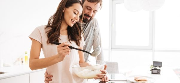 portrait-of-a-happy-young-couple-cooking-pancakes-PEX8TNL.jpg